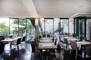 Paneles transparentes con perfilería perimetral que personaliza los espacios exteriores e interiores de un restaurante en Perugia.
