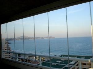 Paneles deslizantes de cristal transparente para el cerramiento exterior de una terraza junto al mar.