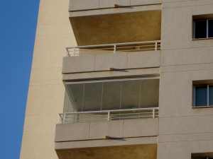 El cerramiento exterior transparente de una terraza situada en un piso alto junto a una playa española.