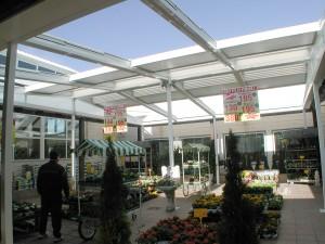 Techo móvil abierto sobre el espacio exterior de una floristería ubicada en un centro comercial.