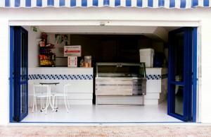 Apertura del cerramiento exterior de una heladería mediante el repliegue de los paneles verticales y plegables de aluminio que permiten climatizar el interior durante todo el año.