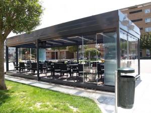 Terraza de un bar de Zizur con paneles deslizantes de cristal sin perfilería que cubren todos los laterales.