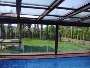 Los paneles deslizantes de cristal sin perfilería facilitan la entrada de luz solar en el espacio interior.