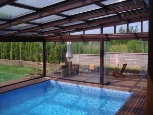 Paneles deslizantes de cristal sin perfilería para las paredes y techo móvil de aluminio en el cerramiento exterior de una piscina.